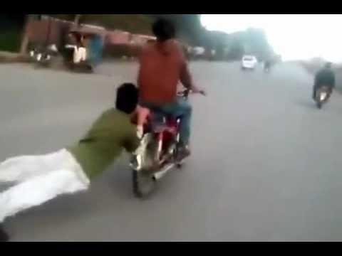 Amateur Stuntman Dangles Behind Motorcycle