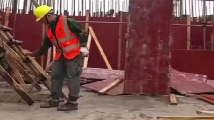 Китайский строитель развлекается в перерыве от работы