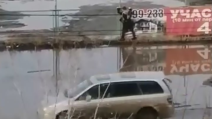 В Омске огромная лужа заставила девушку лезть по забору