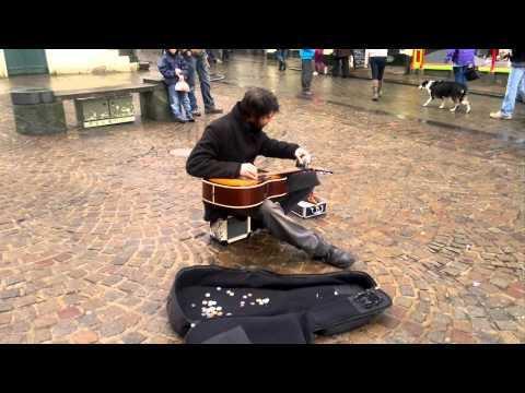 Уличный музыкант играет на гитаре флягой для алкоголя