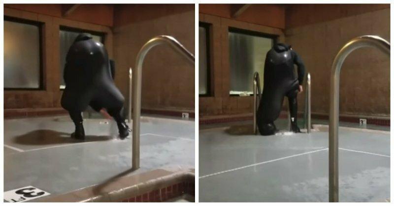 Мужчина пытается слить воду из гидрокостюма