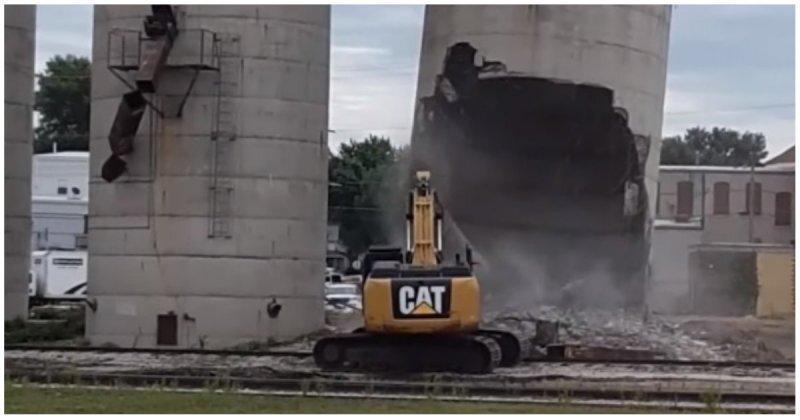Водитель случайно завалил силосную башню на свой экскаватор во время сноса
