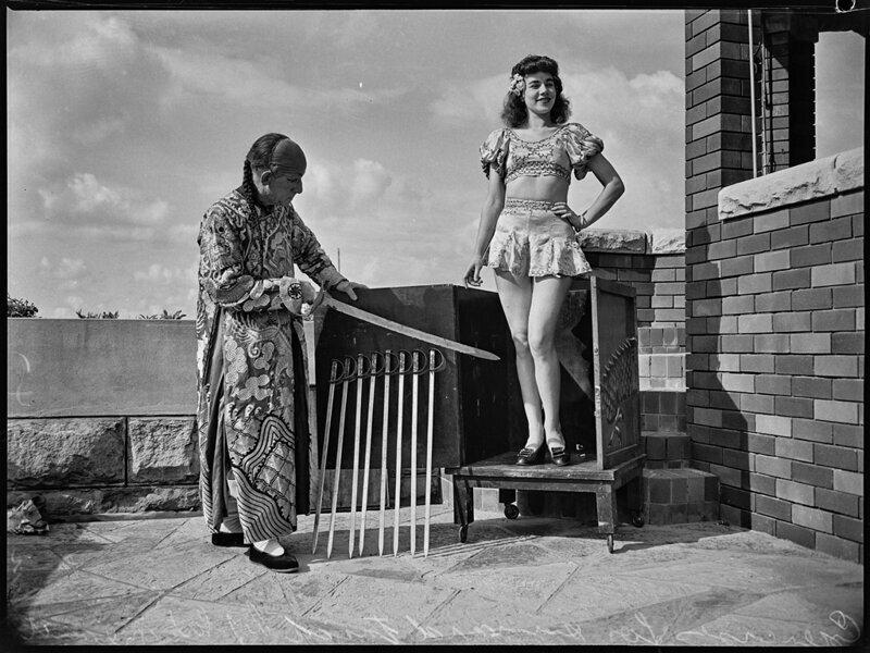 Фокусник со своей помощницей отрабатывают фокус с мечами. 1947