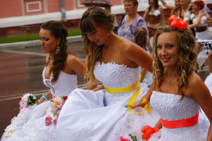 Brides lifting their dresses to walk