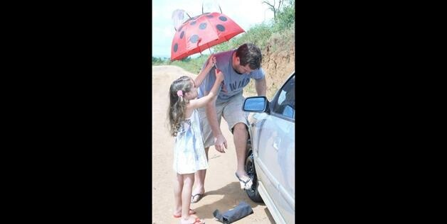 daughter helping father change tire