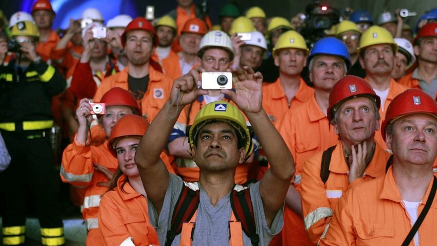 Miners and visitors take pictures as a giant drill machine