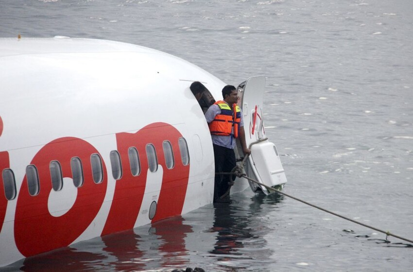 a rescue worker stands at the doorway of a crashed Lion Air plane
