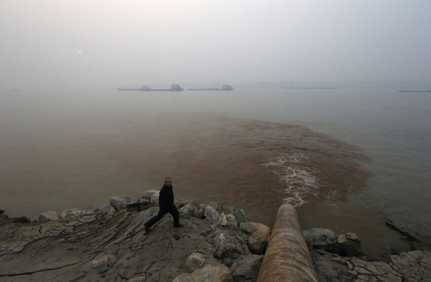 Man Walks By Pipe Discharging Waste Water Into Yangtze River