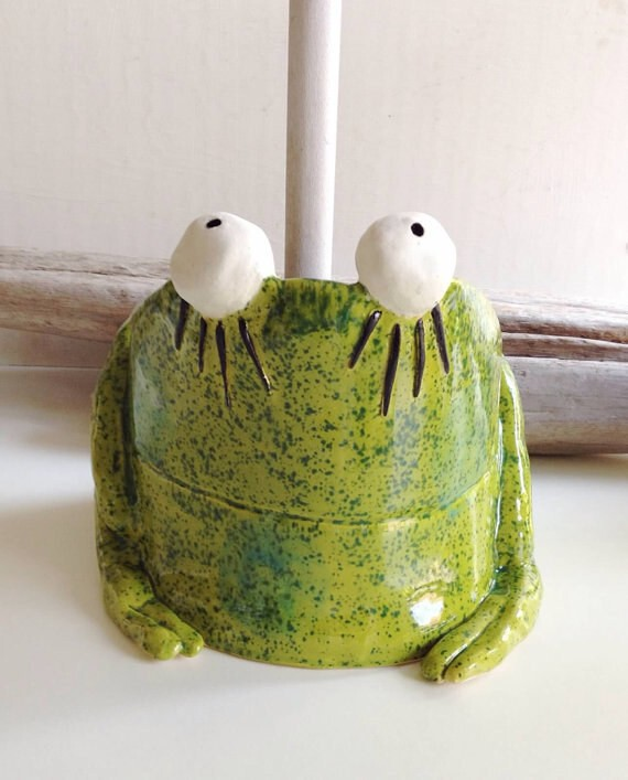 A ceramic frog plunger cover.