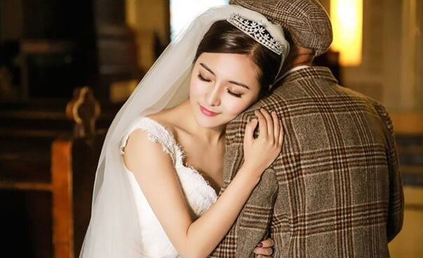 Ms. Fu hugs her grandfather as they walk down the aisle in a church