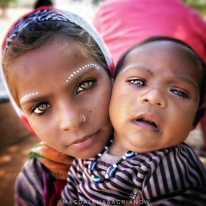 Beautiful Kalbelia girl with her baby sister. Portrait taken in the outskirts of Pushkar