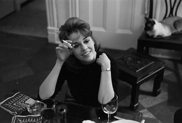 Jane Fonda smoking a cigarette at the dinner table.