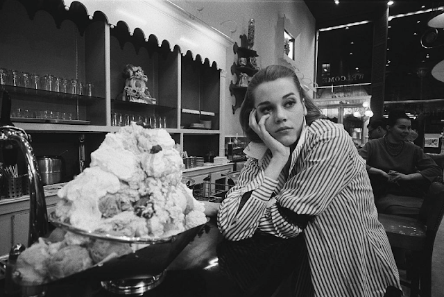 A tired Jane Fonda leaning on the counter at Hicks & Son, where she is working between her classes.