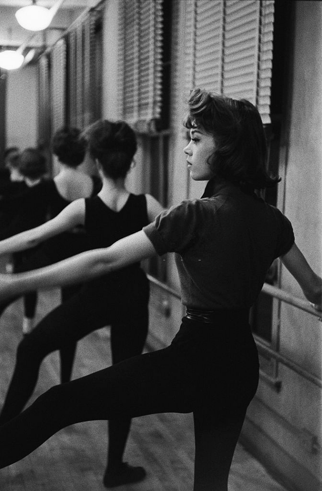 Jane Fonda taking dance lessons in a hall.