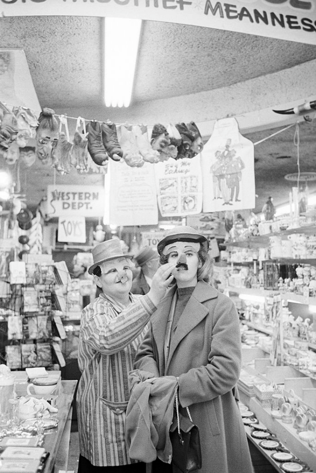 Jane Fonda trying on a mask in a drugstore.