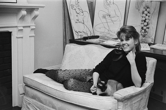 Jane Fonda smiling while lying on the sofa with her Siamese cat at her home.