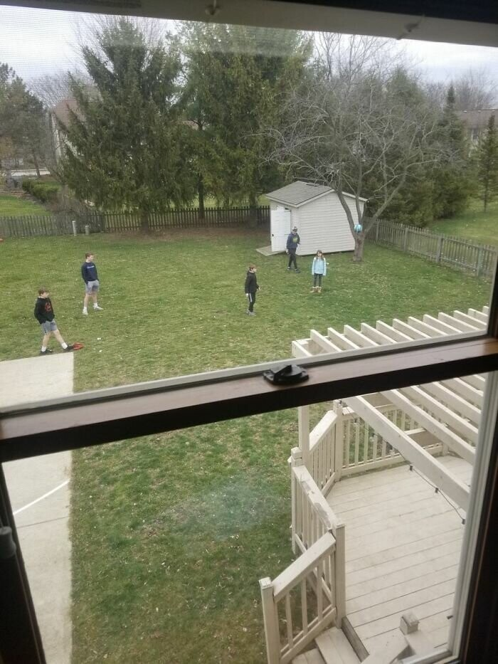 Neighborhood kids in the back--practicing social distancing--playing kickball.
